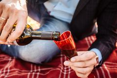 A man pours wine into a glass. Close-up of man`s hand stock photography