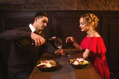 Man pours wine into a glass, couple in restaurant Stock Photo