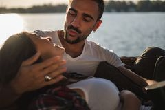 Man pouting while holding his smiling girlfriend by the river. Handsome men pouting while holding his smiling girlfriend by the river on a sunny day royalty free stock images