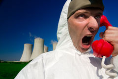 Man at power plant. Man wearing a protective suit talking on the telephone standing in front of a nuclear power plant royalty free stock image