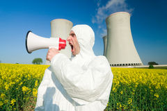 Man at power plant. Man wearing a white jumpsuit yells into a megaphone in front of a power plant royalty free stock image