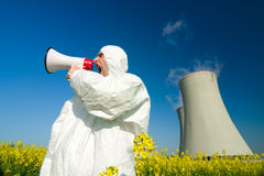 Man at power plant. Man wearing a white jumpsuit yells into a megaphone in front of a power plant royalty free stock images