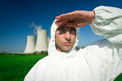 Man at power station. Man in white jumpsuit shielding the sun at a power station stock images