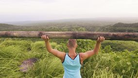 Man powerlifter using timber bar for training in tropical landscape. Sport man lifting wooden barbell for bodybuilding stock footage