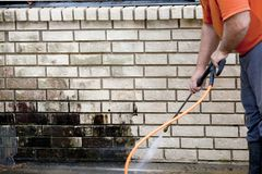 Man powerwashing mold of wall - DIY stock image