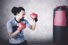 Man practice boxing with sack Royalty Free Stock Photography
