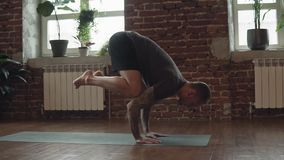 Man practice yoga hand standing pose in studio. Sport and lifestyle concept. Man practice yoga hand standing pose in studio. Fitness, sport and healthy lifestyle stock video footage