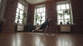 Man practice yoga pose in studio with brick wall. Healthy lifestyle concept. Man practice yoga pose in studio with brick wall and large windows. Attractive man stock video