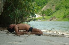 Man practices yoga by river Stock Images