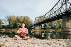 Man practices yoga on the river bank near the old bridge Stock Photo
