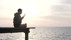 A man practices yoga with a sunset view of the sea. He sits cross-legged on a wooden bridge near the ocean. Young British Tourist practicing raised arms stock video footage