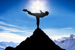 Man Practicing Balancing On A Peak Of A Mountain. Silhouette Of A Man Practicing Balancing On A Peak Of A Mountain Against Snowy Mountains Royalty Free Stock Photo