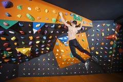 Man practicing bouldering in indoor climbing gym Royalty Free Stock Photos
