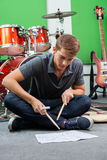 Man Practicing With Drumsticks While Looking At Stock Photo