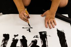 A man practicing Japanese calligraphy.  royalty free stock photography