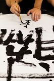 A man practicing Japanese calligraphy.  stock images