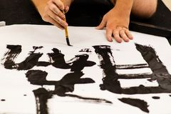 A man practicing Japanese calligraphy. On a big piece of paper stock photography