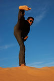 Man practicing karate. On toop of a sand dune Stock Photos