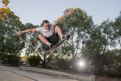 Man practicing radical skate board jumping and enjoying tricks and stunts in concrete half pipe skating track in sport and healthy. Young American man practicing stock images