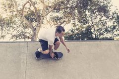 Man practicing radical skate board jumping and enjoying tricks and stunts in concrete half pipe skating track in sport and healthy. Young American man practicing stock photos