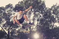 Man practicing radical skate board jumping and enjoying tricks and stunts in concrete half pipe skating track in sport and healthy. Young American man practicing stock photography