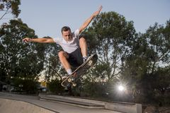 Man practicing radical skate board jumping and enjoying tricks and stunts in concrete half pipe skating track in sport and healthy. Young American man practicing stock photo