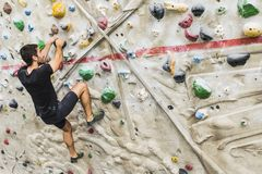 Man practicing rock climbing on artificial wall indoors. Active Royalty Free Stock Image