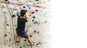Man practicing rock climbing on artificial wall indoors. Active Royalty Free Stock Photo