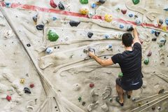 Man practicing rock climbing on artificial wall indoors. Active Stock Photography