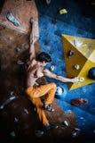Man practicing rock-climbing. Muscular man practicing rock-climbing on a rock wall indoors Royalty Free Stock Photos