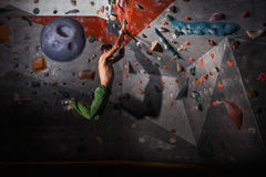 Man practicing rock-climbing on a rock wall indoors stock image