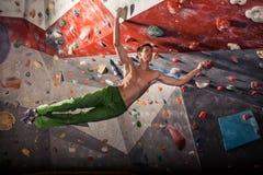 Man practicing rock-climbing on a rock wall indoors Royalty Free Stock Photos