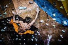 Man practicing rock-climbing on a rock wall Stock Image