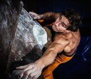 Man practicing rock-climbing on a rock wall Royalty Free Stock Photos