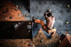 Man practicing rock-climbing on a rock wall Stock Photos