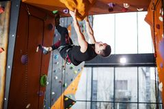 Man practicing top rope climbing in climbing gym Stock Images