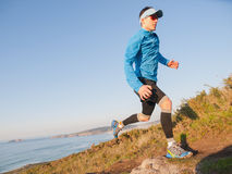 Man practicing trail running in a coastal landscape Royalty Free Stock Image