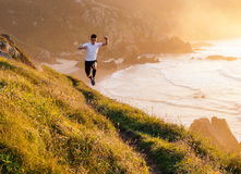 Man practicing trail running and leaping in a path in the coast Royalty Free Stock Image