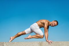 Man practicing yoga blue sky background. Reached peace of mind. Meditation and yoga concept. Yoga helps find balance. Practice asana outdoor. Yoga practice stock images