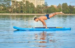 Man practicing yoga, doing balance body weight smimming on paddle board. Muscular man practicing yoga, doing balance body weight, swimming on paddle board in royalty free stock photo