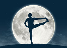 Man practicing yoga at full moon. Silhouette of a young man practicing yoga with the full moon on the background Stock Images