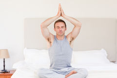 Man practicing yoga on his bed Royalty Free Stock Photos