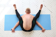 Man practicing yoga. Kurmasana. Tortoise pose. Tortoise posture. Top view Royalty Free Stock Images