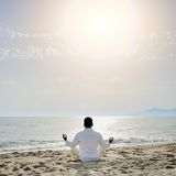 Man practicing yoga meditation exercises on the be Stock Photos