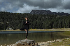 Man practicing yoga near the Autumn Black Lake, Durmitor Nationa Stock Image