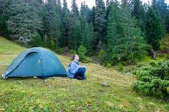 Man practicing yoga near blue camping tent Stock Photos
