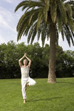 Man Practicing Yoga In Park Stock Photo