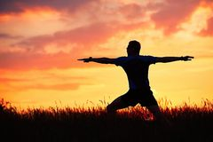 Man is practicing yoga during sunset Stock Photo