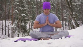 Man practicing yoga in the woods in nature in winter Royalty Free Stock Photos