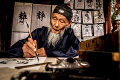 Man practising Chinese calligraphy at the Summer P. An old man practises Chinese calligraphy (hanzi) at the Summer Palace in Beijing, China. (circa June 2013 Royalty Free Stock Photos